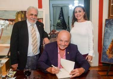Joaci Góes autografando o livro para Frances e Giovanni Pisano cônsul da Itália em fotos de Valterio